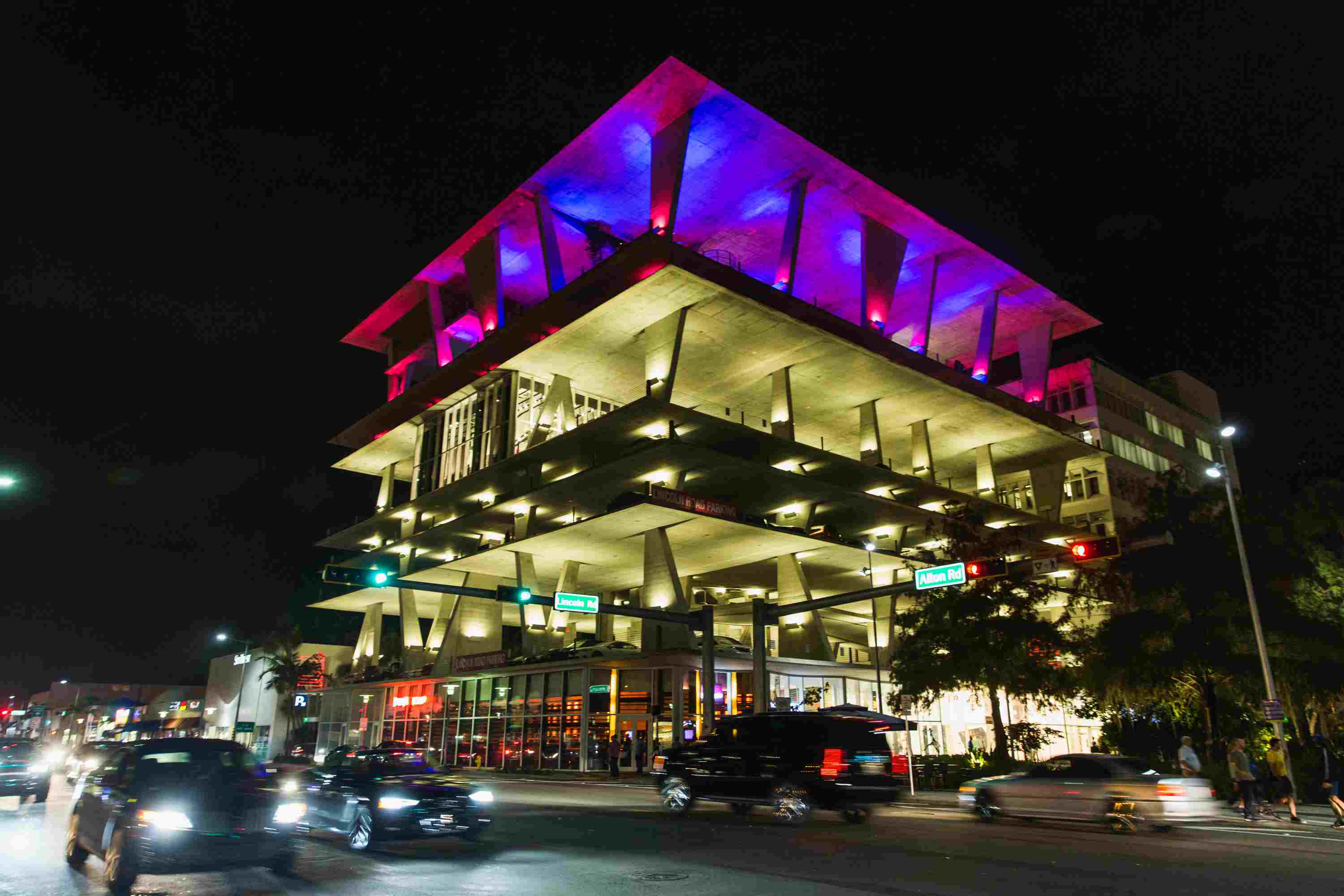night view of multi-level parking garage, lit with purple lights on the top floor