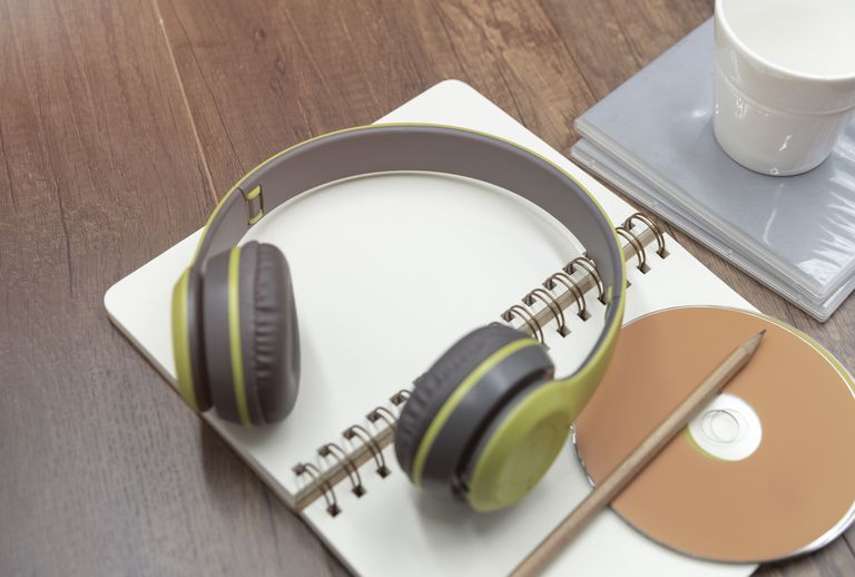 Headphone, CD, pencil and a cup of water on the diary book, music relaxing concept.