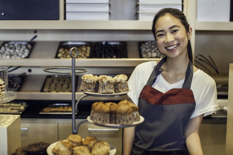 Woman smiling behind bakery counter, portrait