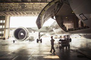 A man is checking a plane door in a hangar