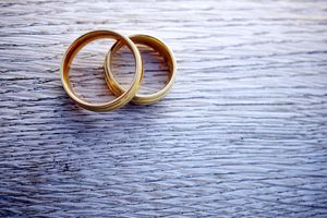 A pair of gold wedding rings on a wooden table