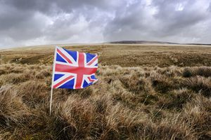 British flag on a hill under a cloudy, gray sky.