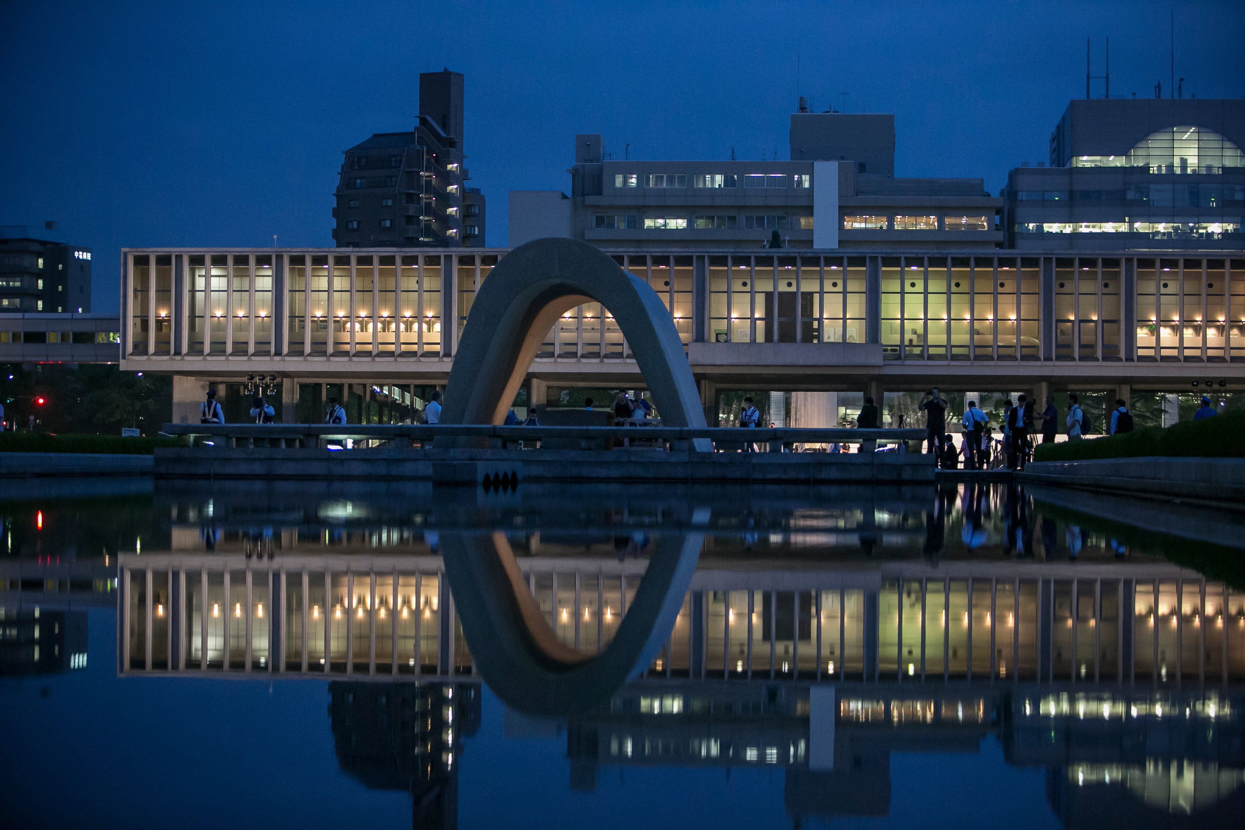 The arch and the Peace Memorial Museum reflected in the water inside Peace Memorial Park in Hiroshima, Japan