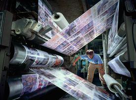 Man observing web press printing