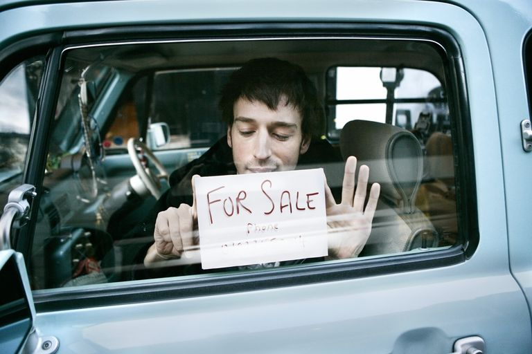 Man putting up 'for sale' sign in car, view through window