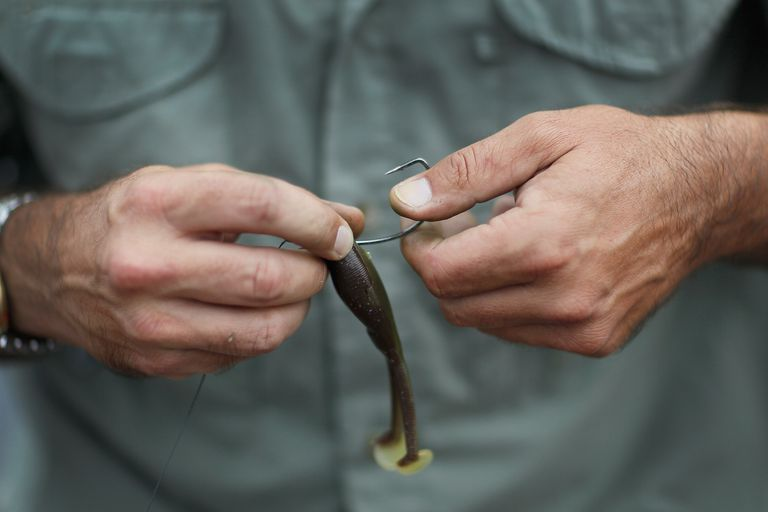 man putting lure on fishing hook