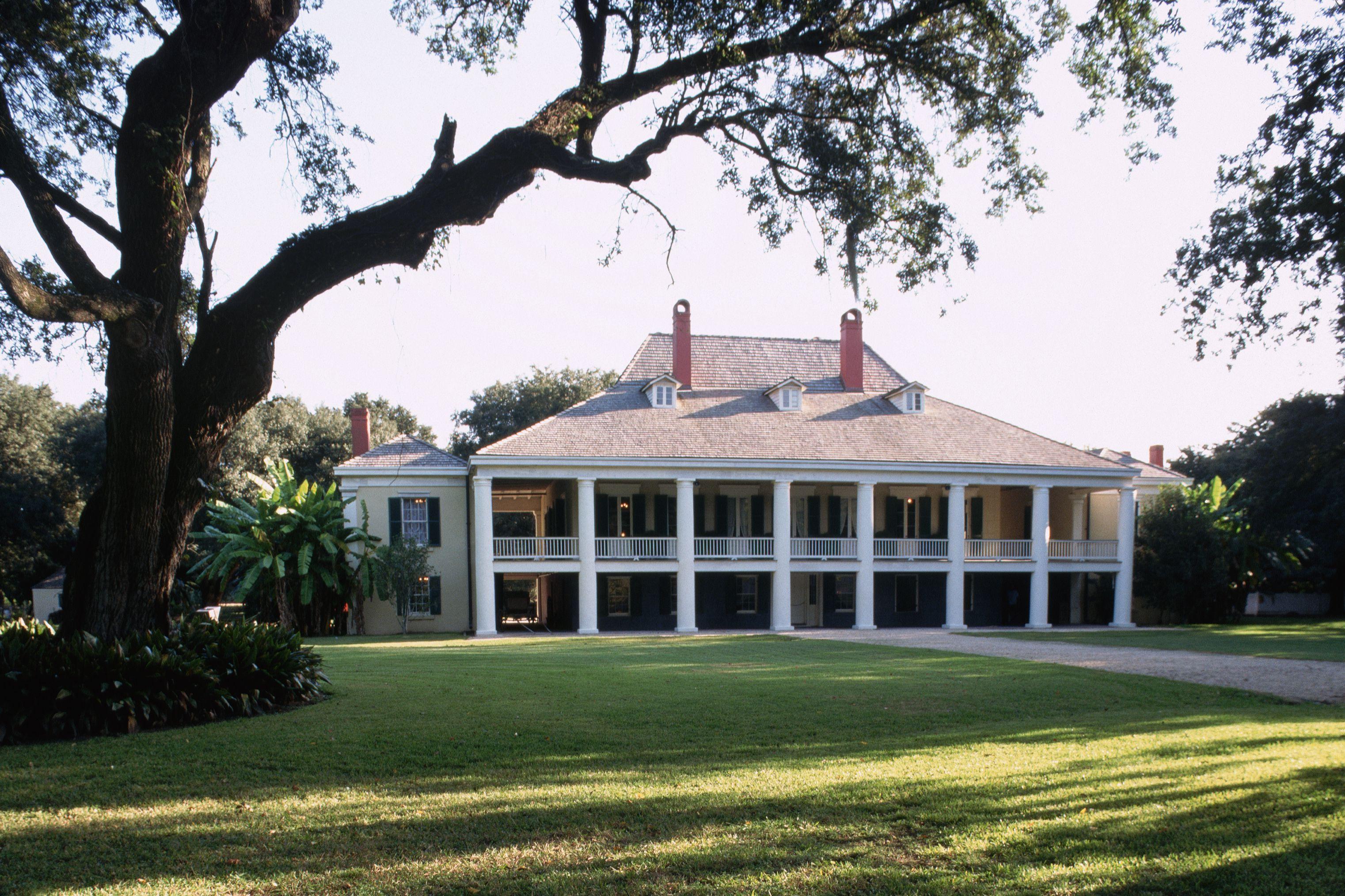 grand manoir de plantation, deux étages avec balcons à colonnes, toit en croupe