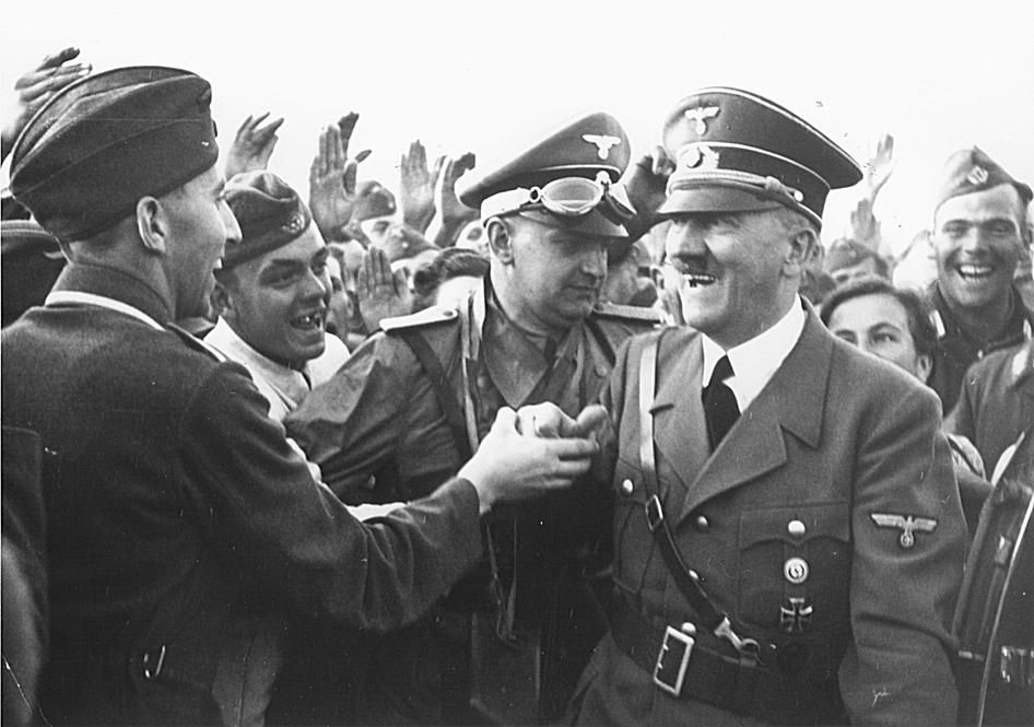 A smiling Adolf Hitler greets a soldier.