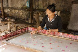 Woman placing petals in handmade paper.