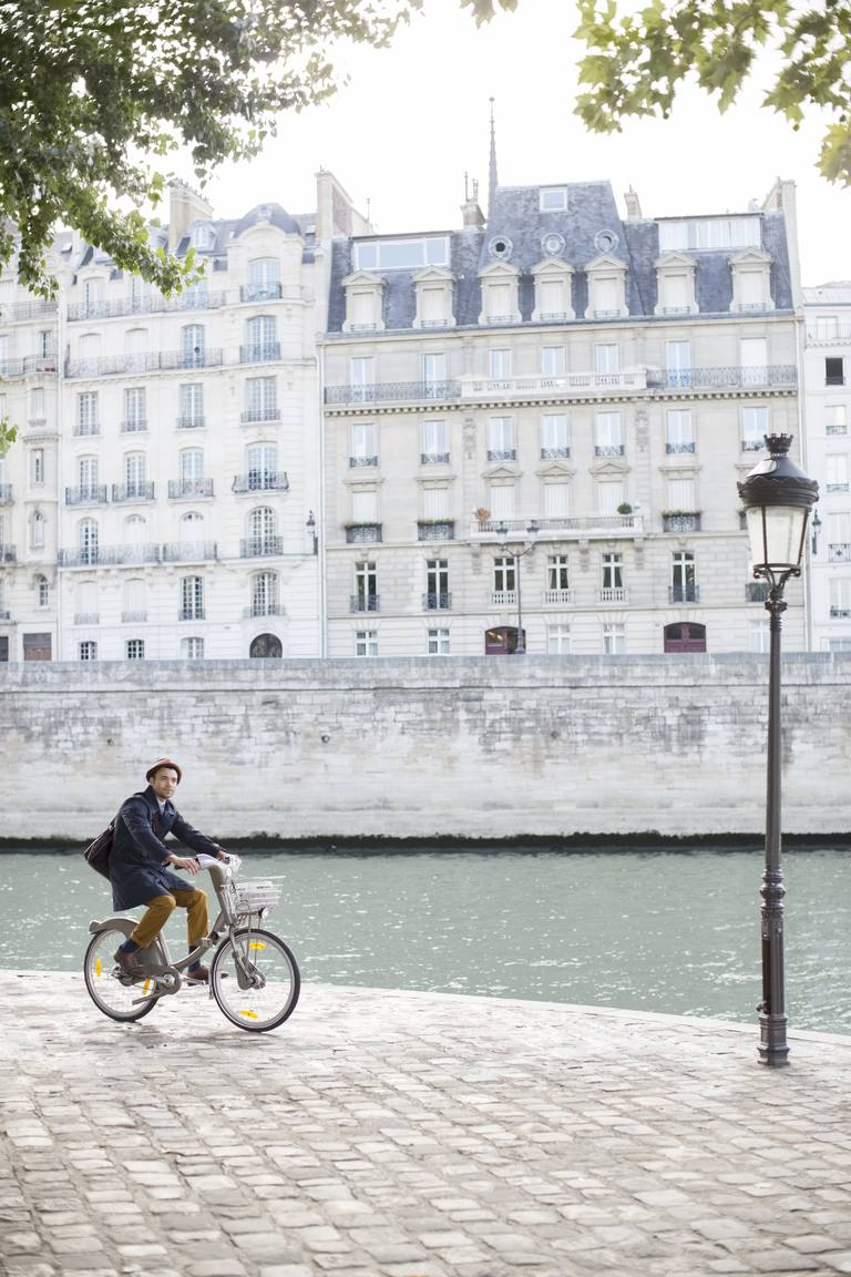Man riding bicycle along Seine River, Paris, France