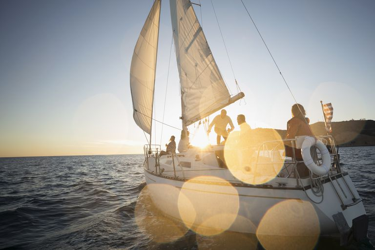 Friends sailing on sunset sailboat