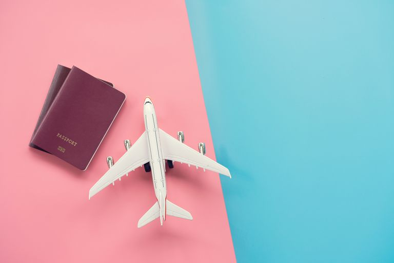 High Angle View Of Airplane Model With Passports On Colored Background