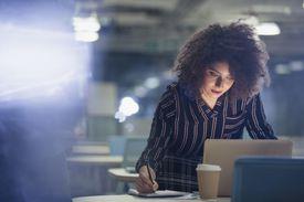 Focused businesswoman working at laptop in dark office.