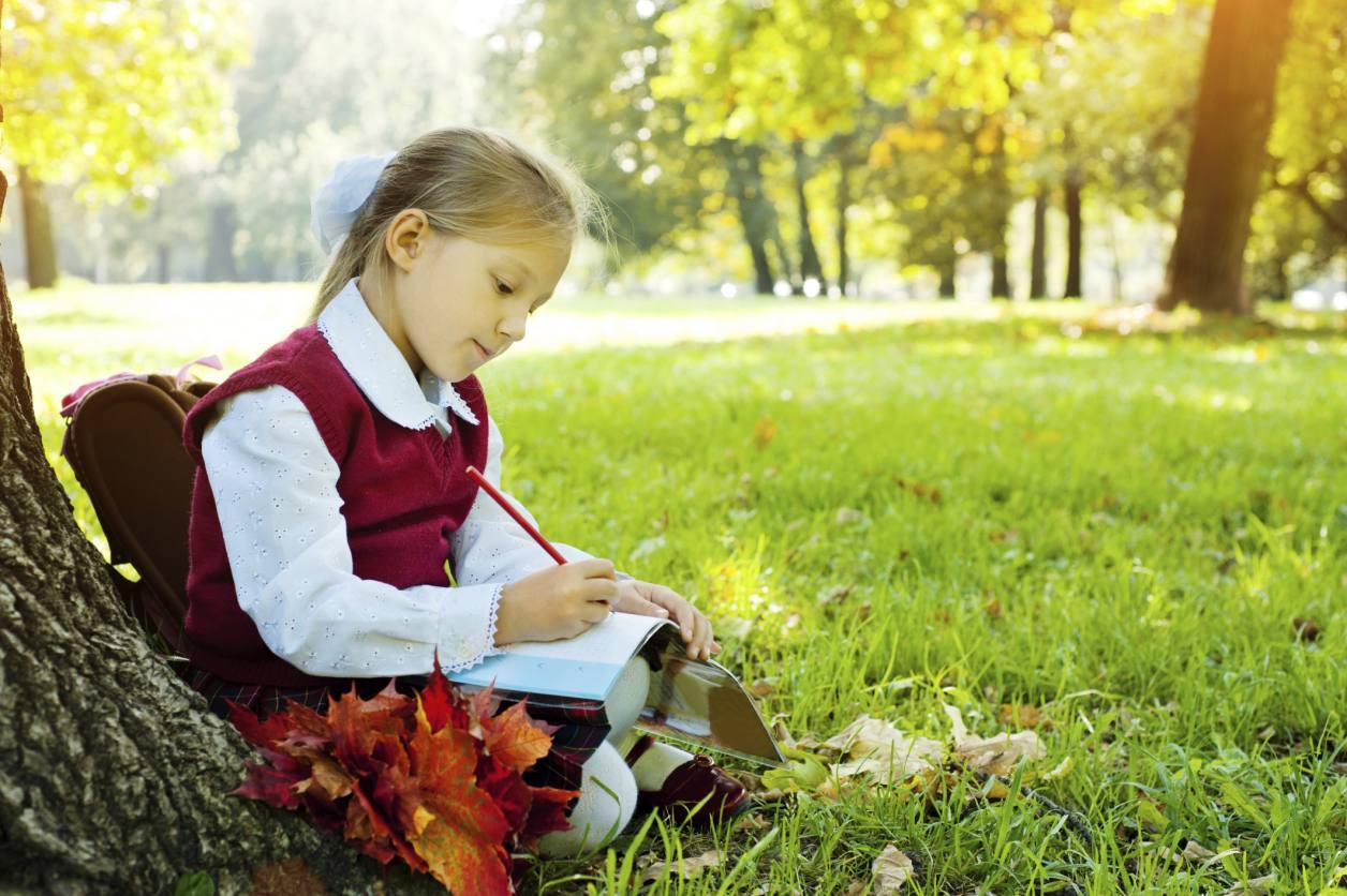 Ein Mädchen, das unter einem fallenden Baum sitzt und in ein Buch schreibt.