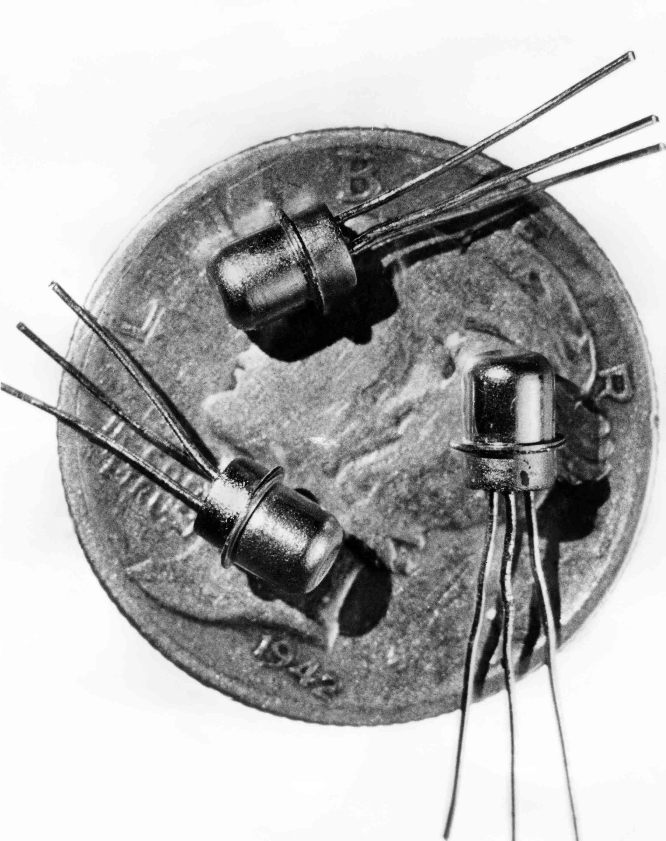 Picture dated 1956 of three miniature M-1 transistors seen on the face of a dime