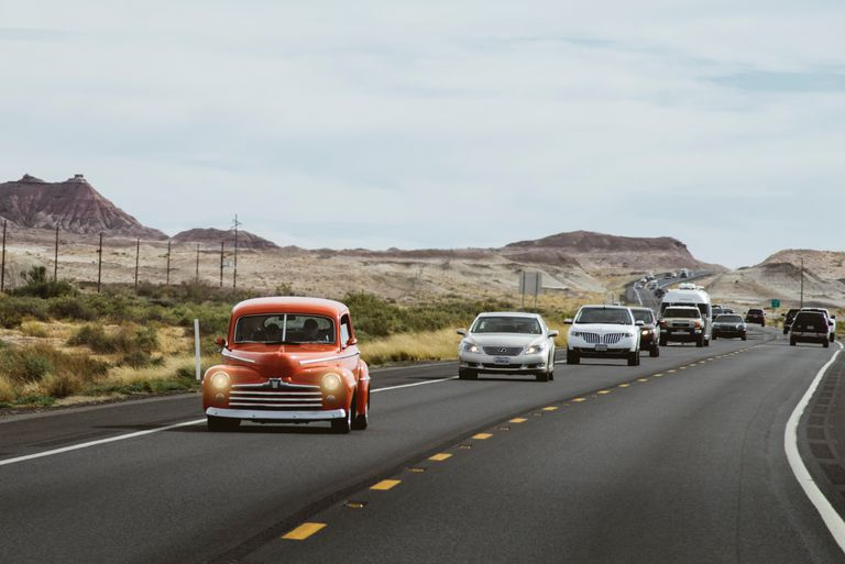 Cars driving along a highway in the desert.