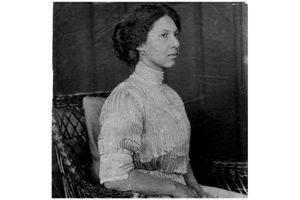 Meta Vaux Warrick Fuller sits on a wicker chair, poised for a photo