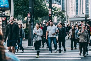 People at a crosswalk in a crowded city.