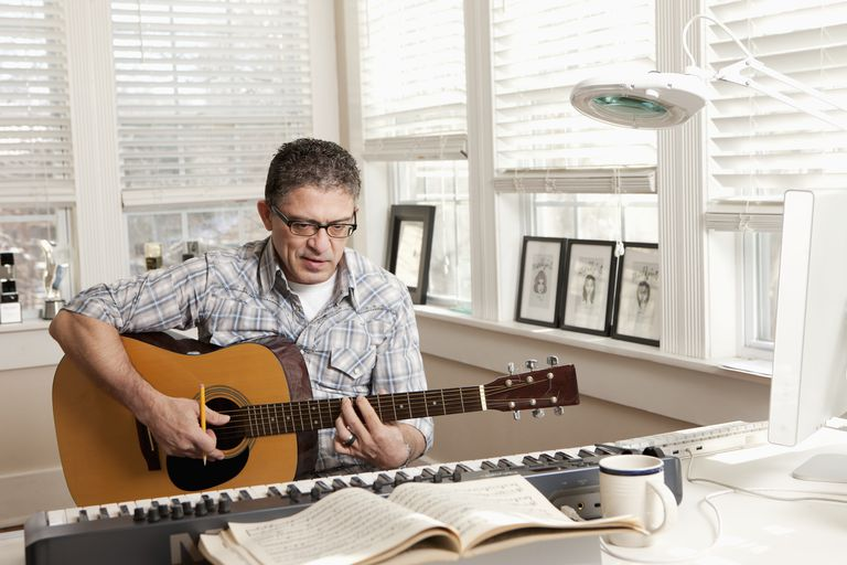 Hispanic man composing music on guitar