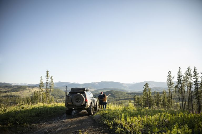 Couple on an overland adventure, looking at remote mountain view next to SUV, Alberta, Canada