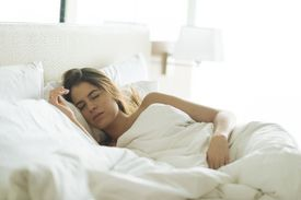 Young woman asleep in hotel bed