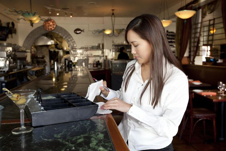 Restaurant employee tallying receipts