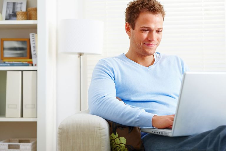 Young Man Using Laptop and Smiling