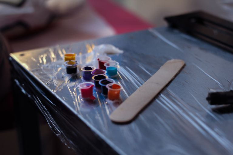 High Angle View Of Colorful Tattoo Inks In Plastic Containers On Table