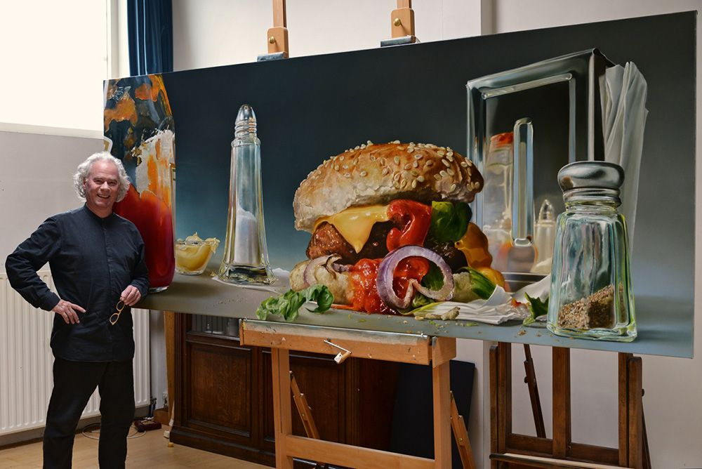 Man stands with oversized image of a hamburger and salt and pepper shakers.