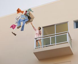 woman throwing clothes off balcony