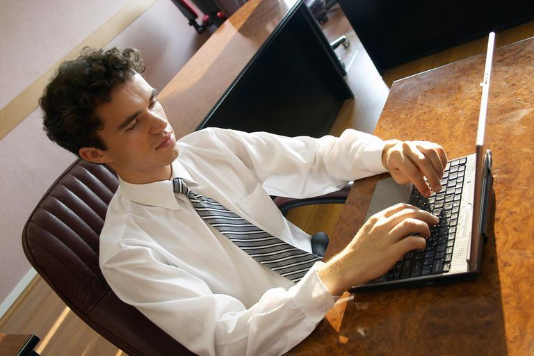 A young businessman is working at his notebook in his office.