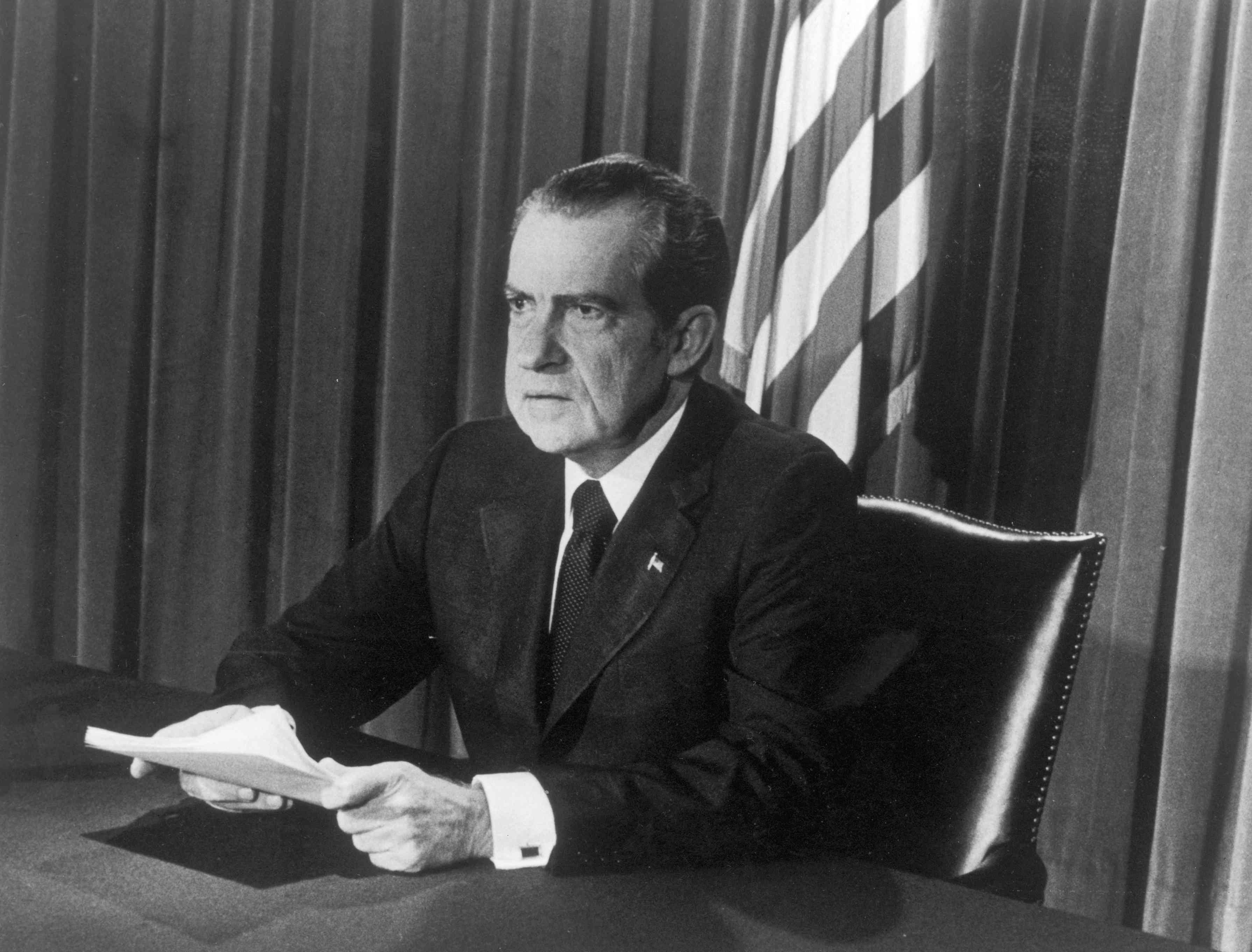 Richard Nixon sits at a desk with papers in hand