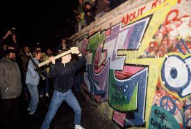 A man attacks the Berlin Wall with a pickaxe on the night of November 9th, 1989