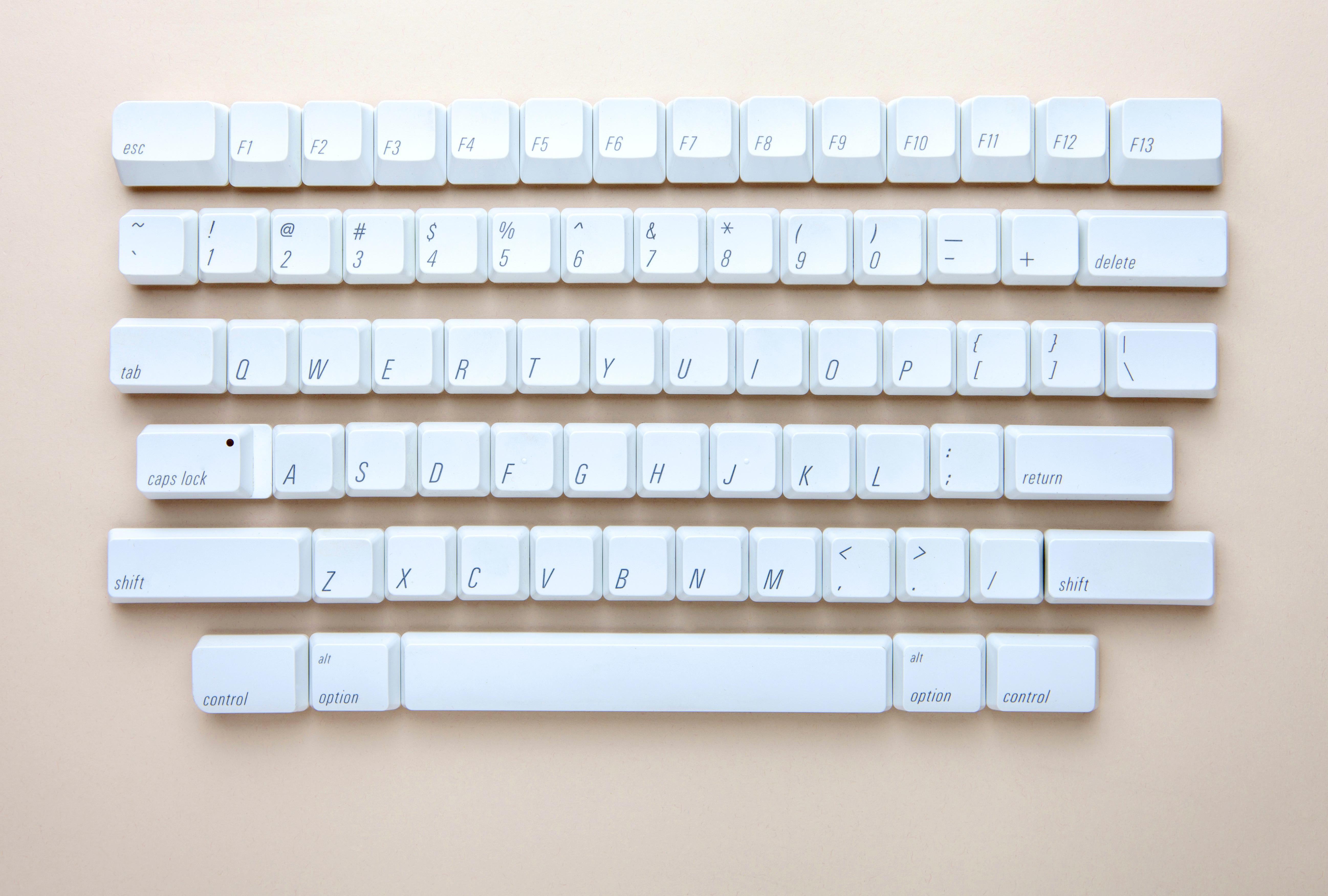 Dismantled keyboard on pink background.
