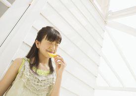 Girl eating a lemon outside
