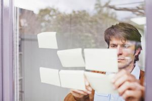 Businessman with sticky notes on window