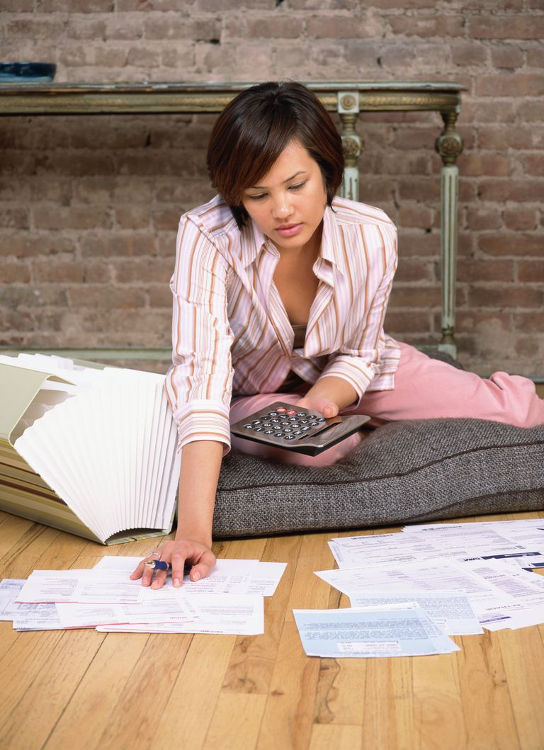 Woman sitting on the floor with a calculator looking over bills