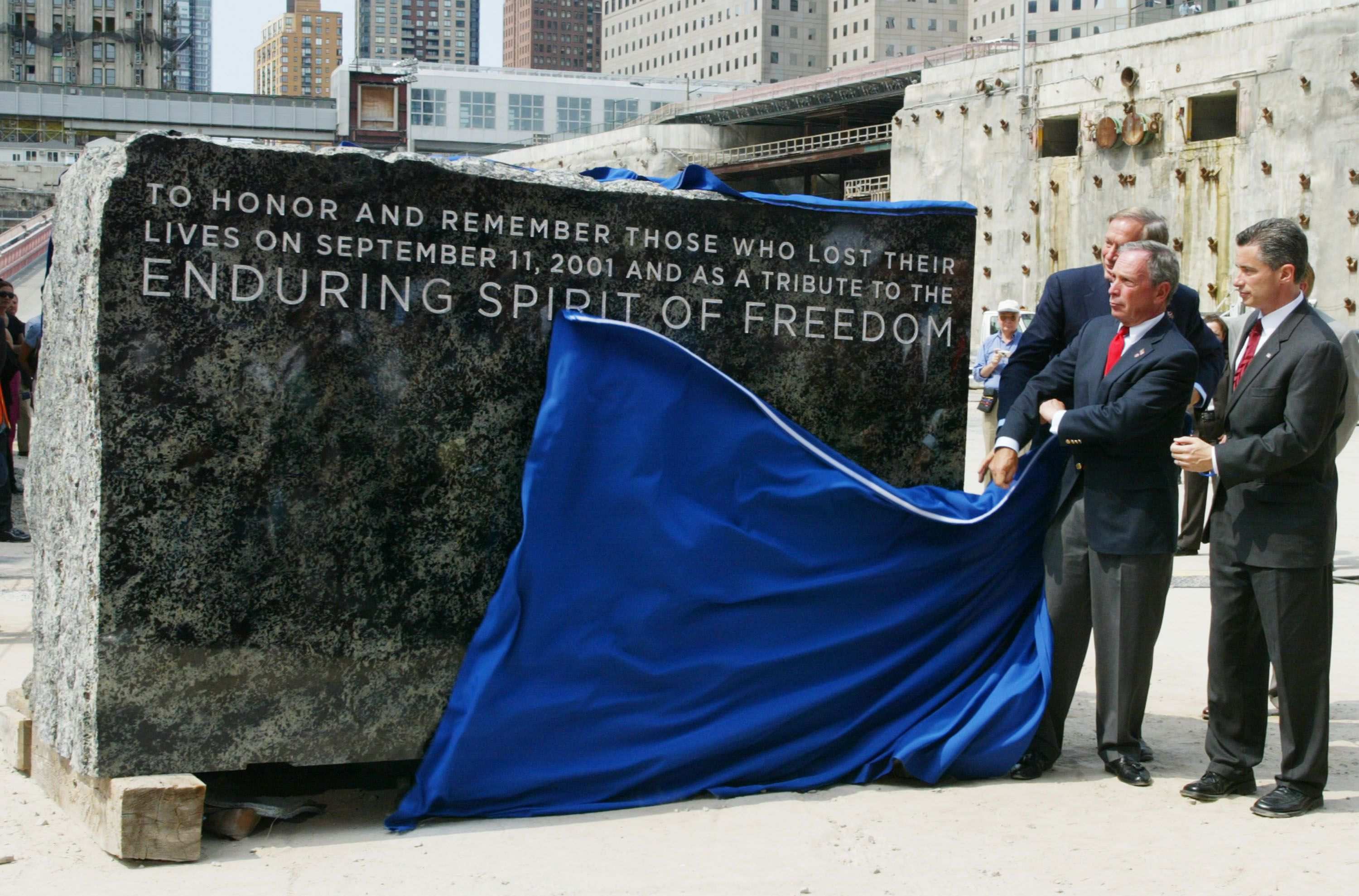 white men in suits and red ties unfurl a blue tarp from an engraves pieces of stone that says To honor and remember those who lost their lives on September 11, 2001 and as a tribute to the enduring spirit of Freedom
