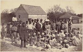 Photograph of American slaves on a farm.