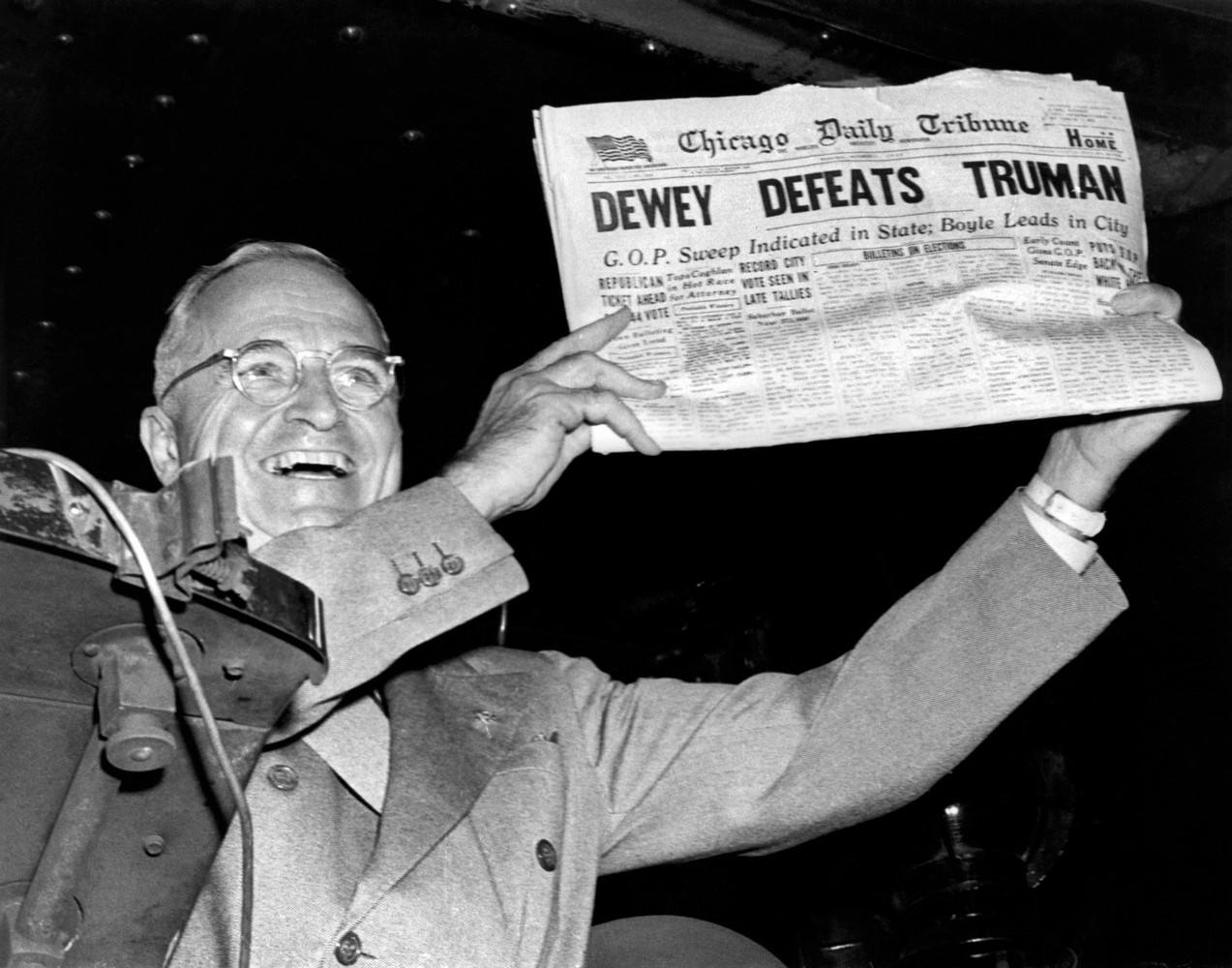 President Harry Truman holding up a newspaper with headline proclaiming, 'Dewey Defeats Truman.'