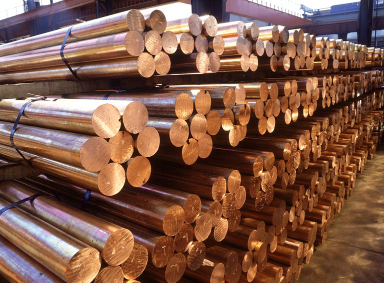 Round bars of copper stored in a warehouse ready for delivery to a manufacturer.