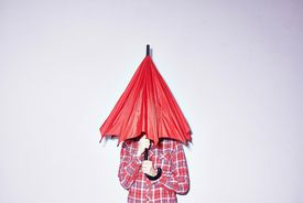Studio shot of young woman holding red umbrella over her head.