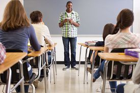 Male high school student giving speech in front of a class of students