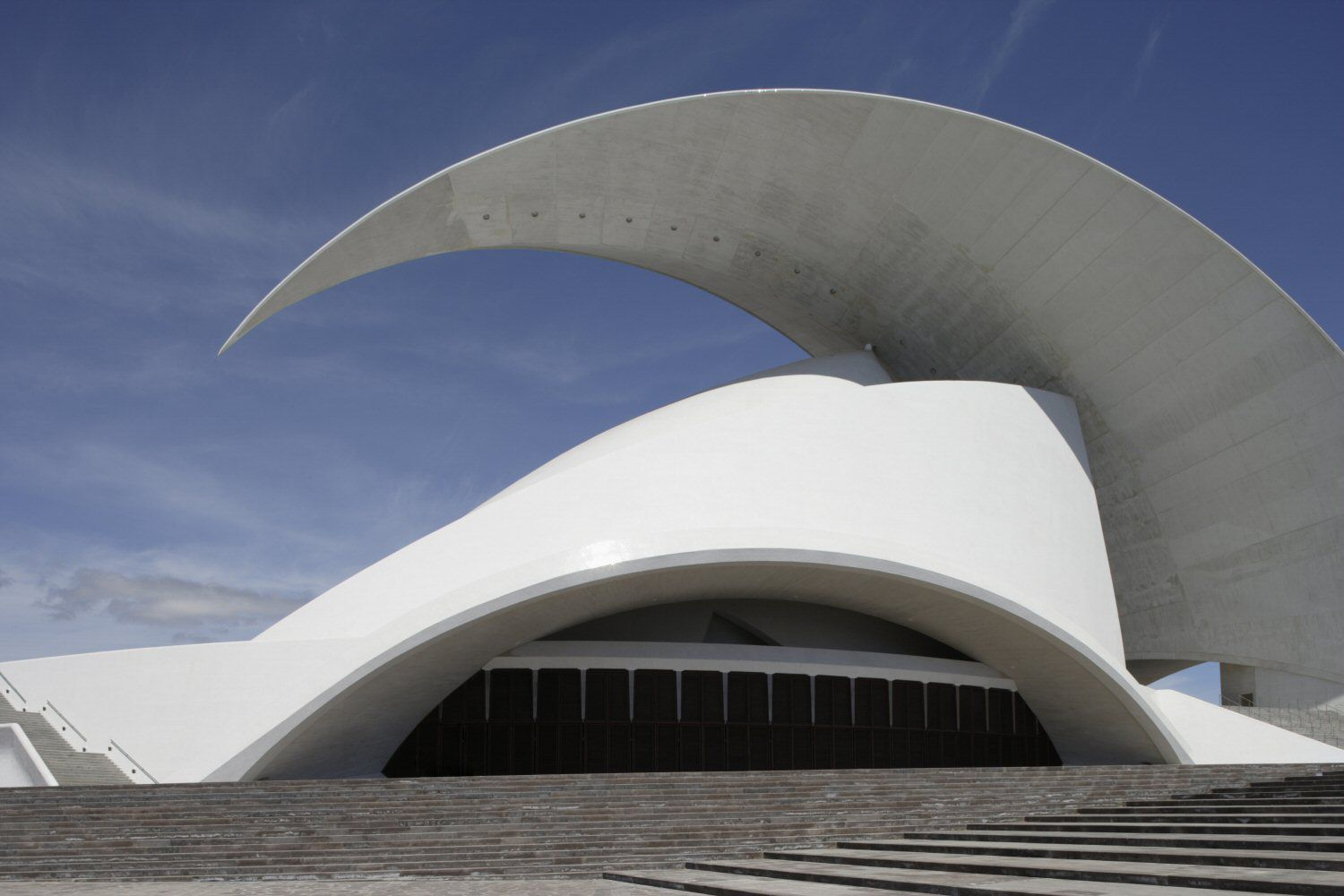 Photo of bright white modern concert hall, with sweeping curved arc-wave above the roof.