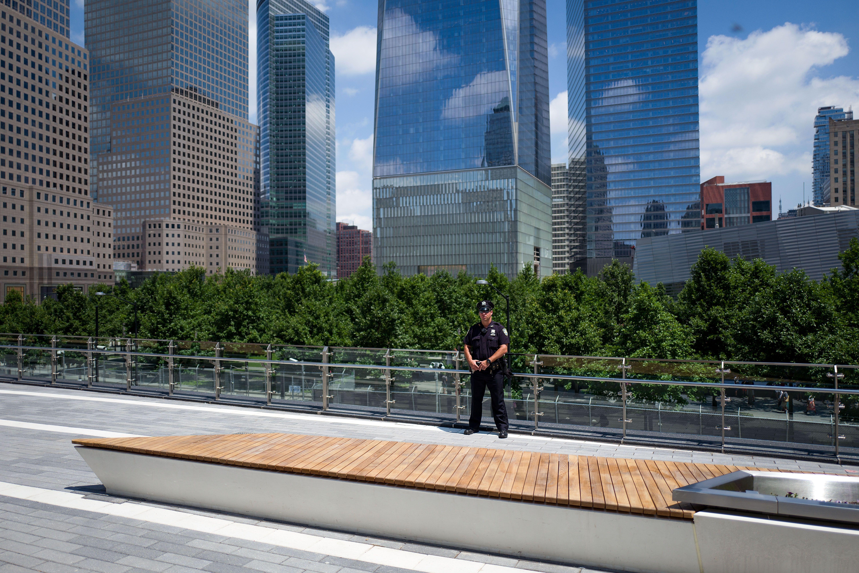 debout policier près de la balustrade du parc avec vue sur les gratte-ciel et cime des arbres