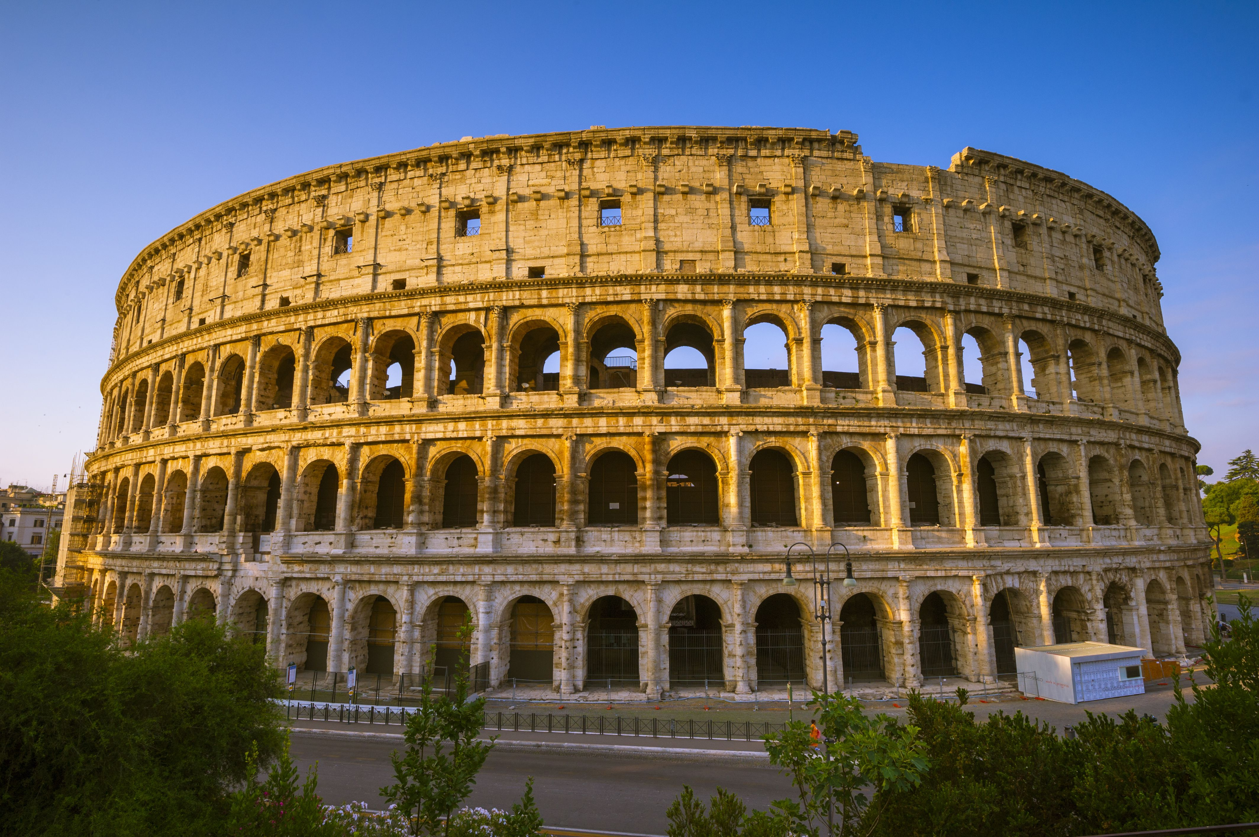 Roman Colosseum at sunrise, three stories of arches and top story of pilasters and rectangular openings