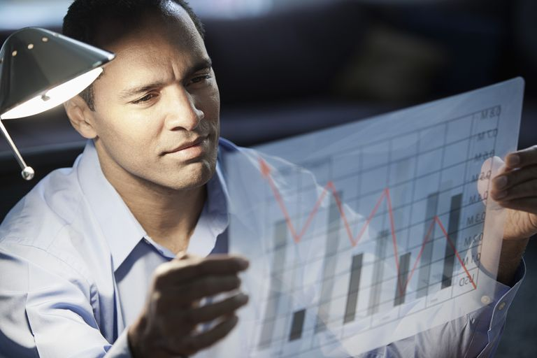 Businessman looking at bar graph chart