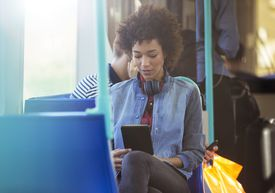 Woman on a bus using electronic device