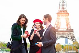 Friends with smartphones near the Eiffel tower in Paris.