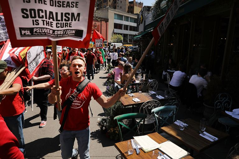 """A march for workers' rights, with a man in a red shirt in the foreground with a sign reading """"Socialism is the Cure"""""""